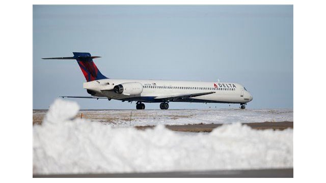 In this photograph taken late Monday, Feb. 8, 2016, a Delta Airlines craft waits to take off from a runway at Denver International Airport. (AP Photo/David Zalubowski)