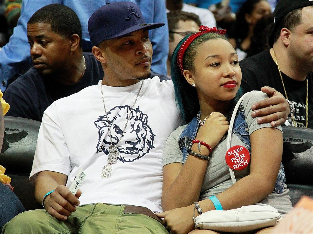 Recording artist and actor T.I. sits with his step daughter Zonnique Pullins, of OMG Girlz, during Game 2 of an NBA first-round playoff series basketball game Tuesday, May 1, 2012, in Atlanta. (AP Photo/John Bazemore)