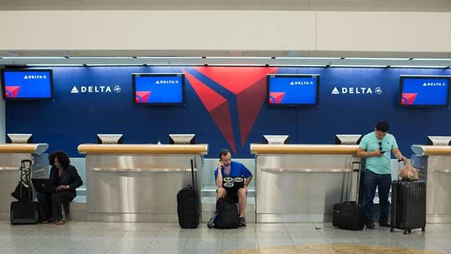 Passengers wait at Hartsfield–Jackson Atlanta International Airport, Monday, Aug. 8, 2016, in Atlanta. Delta Air Lines delayed or canceled hundreds of flights Monday after its computer systems crashed, stranding thousands. (AP Photo/Branden Camp)