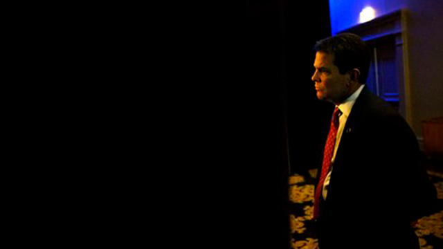 Georgia Secretary of State Brian Kemp looks out through a curtain while waiting for New Jersey Gov. Chris Christie, not pictured, to leave a speaking engagement ahead of this afternoon's convening of the Georgia Republican Convention.