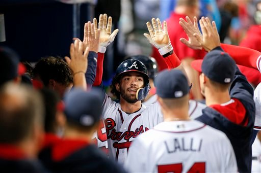 Atlanta Braves' Dansby Swanson celebrates in the dugout after hitting a a solo home run in the sixth inning of a baseball game against the Philadelphia Phillies, Thursday, Sept. 29, 2016, in Atlanta. (AP Photo/Brett Davis)