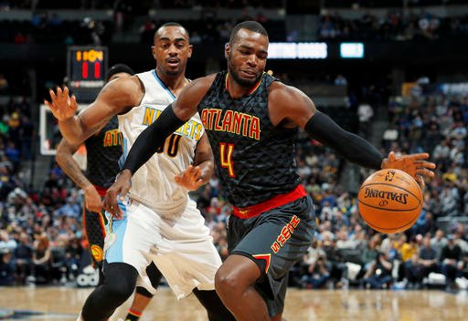 Atlanta Hawks forward Paul Millsap, front, reaches back for a loose ball as Denver Nuggets forward Darrell Arthur defends in the second half of an NBA basketball game Friday, Dec. 23, 2016, in Denver. The Hawks won 109-108. (AP Photo/David Zalubowski)