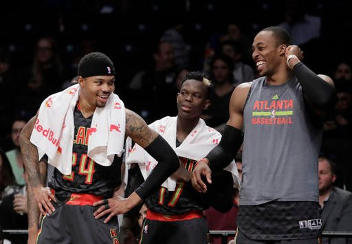Atlanta Hawks' Kent Bazemore, left; Dennis Schroder, center, of Germany; and Dwight Howard, right, smile during the second half of the team's NBA basketball game against the Brooklyn Nets on Tuesday, Jan. 10, 2017, in New York.  (AP Photo)