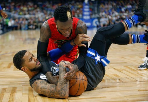 Atlanta Hawks guard Dennis Schroder, top, fights for the ball with Orlando Magic guard D.J. Augustin during the second half of an NBA basketball game in Orlando, Fla., Saturday, Feb. 25, 2017. (AP Photo/Reinhold Matay)