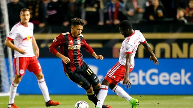 Atlanta United midfielder Yamil Asad (11) is tripped up by New York Red Bulls defender Kemar Lawrence (92) in the second half of an MLS soccer game on Sunday, March 5, 2017, in Atlanta. The New Yourk Red Bulls won the game 2-1. (AP Photo/Todd Kirkland)
