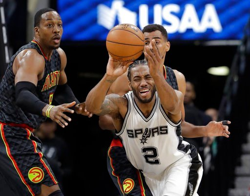 San Antonio Spurs forward Kawhi Leonard (2) tries to work the ball between Atlanta Hawks defenders Dwight Howard (8) and Thabo Sefolosha (25) during the second half of an NBA basketball game, Monday, March 13, 2017, in San Antonio.(AP Photo/Eric Gay)