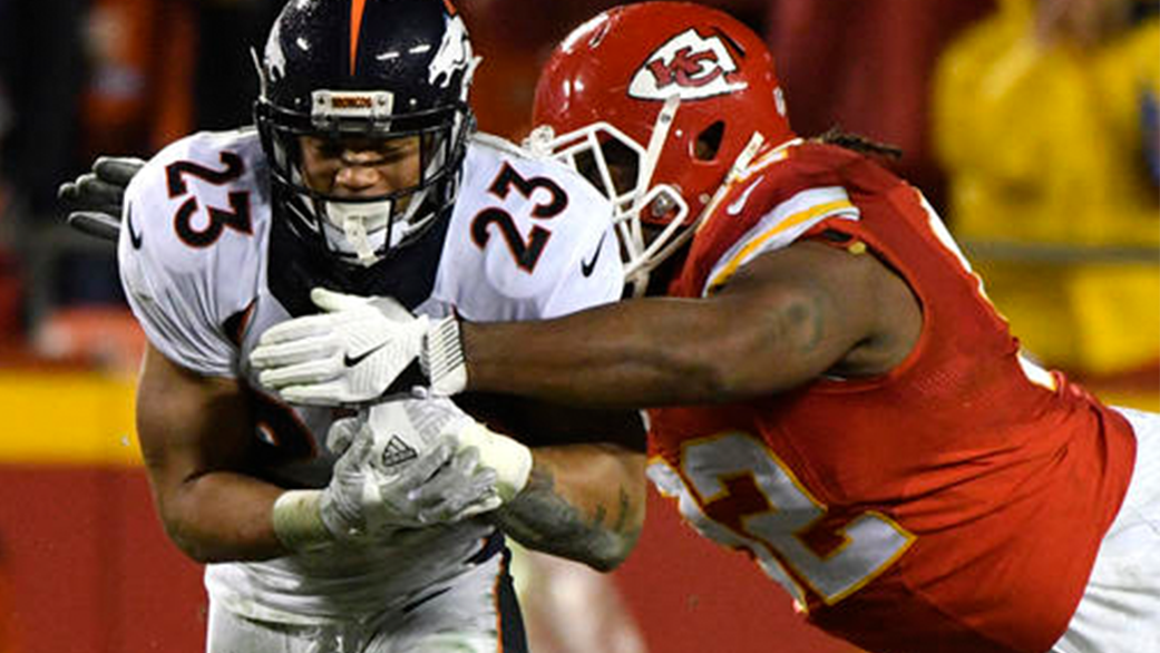 Kansas City Chiefs defensive lineman Dontari Poe (92) tackles Denver Broncos running back Devontae Booker (23) during the first half of an NFL football game in Kansas City, Mo., Sunday, Dec. 25, 2016. (AP Photo/Ed Zurga)