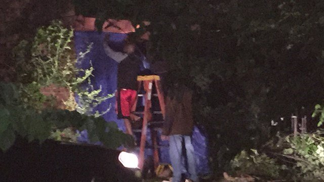 A DeKalb County homeowner works to put a blue tarp over the side of his home where a driver reportedly ran his vehicle into it Monday morning April 24, 2017. (SOURCE: WGCL)