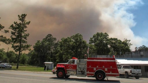 A fire truck passes as a plume of smoke rising from a wildfire burning, Monday, May 8, 2017, just outside the town of St. George, Ga. Officials placed the town under a mandatory evacuation after winds pushed the fire out of the neighboring Okefenokee Nati
