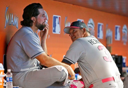 Atlanta Braves starting pitcher R.A. Dickey, left, talks with pitching coach Chuck Hernandez during the eighth inning of a baseball game against the Miami Marlins, Sunday, May 14, 2017, in Miami. The Marlins defeated the Braves 3-1 (AP Photo/Wilfredo Lee)