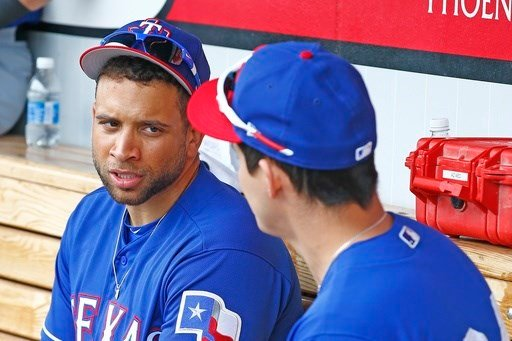 Texas Rangers first baseman James Loney, left, talks with Jose Cardona, right, prior to a spring training baseball game against the Cleveland Indians Monday, Feb. 27, 2017, in Goodyear, Ariz. (AP Photo/Ross D. Franklin)