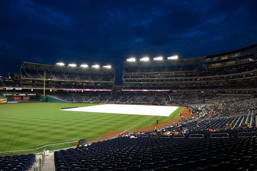 The tarp lies on the field during a delay before a baseball game between the Washington Nationals and the Atlanta Braves, Thursday, July 6, 2017, in Washington. (AP Photo/Nick Wass)