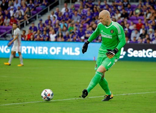 Atlanta United goalkeeper Brad Guzan clears the ball to a teammate during the first half of an MLS soccer match against Orlando City, Friday, July 21, 2017, in Orlando, Fla. (AP Photo/John Raoux)