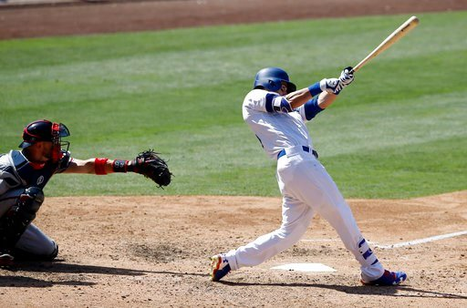 Los Angeles Dodgers' Cody Bellinger, right, hits a solo home run with Atlanta Braves catcher Tyler Flowers watching during the eighth inning of a baseball game in Los Angeles, Sunday, July 23, 2017. (AP Photo/Alex Gallardo)