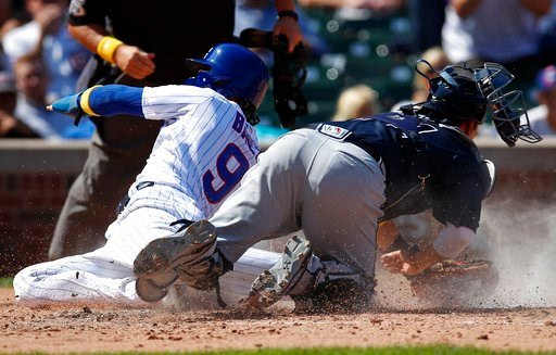 Chicago Cubs second baseman Javier Baez (9) slides safely into home plate past a tag by Atlanta Braves catcher Kurt Suzuki (24) during the third inning of a baseball game Friday, Sept. 1, 2017, in Chicago. (AP Photo/Jim Young)