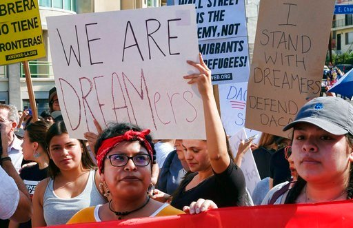 (AP Photo/Richard Vogel). Supporters of the Deferred Action for Childhood Arrivals, or DACA chant slogans and hold signs while joining a Labor Day rally in downtown Los Angeles on Monday, Sept. 4, 2017.