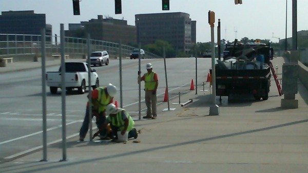 Crews work to block of the south sidewalk after the fence accident