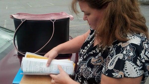 Margarita Segers looks through her paperwork