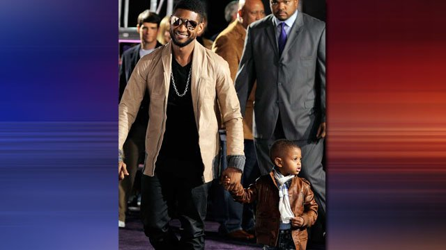 Usher, center, arrives with his son, Usher Raymond V, at the premiere of the documentary film 'Justin Bieber: Never Say Never,' in Los Angeles, Tuesday, Feb. 8, 2011. (AP Photo/Chris Pizzello)