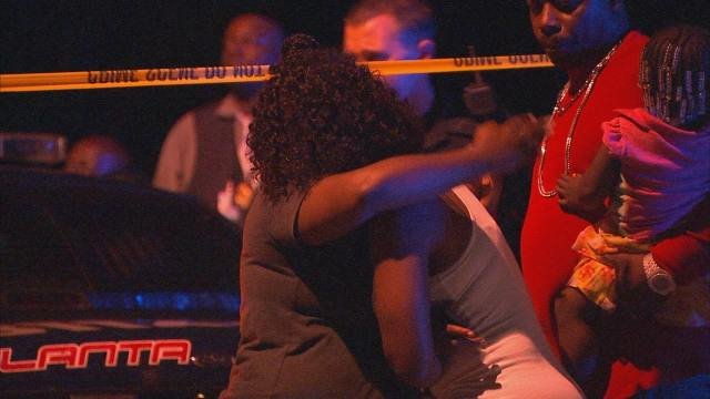 Loved ones of victim embrace at scene of killing.