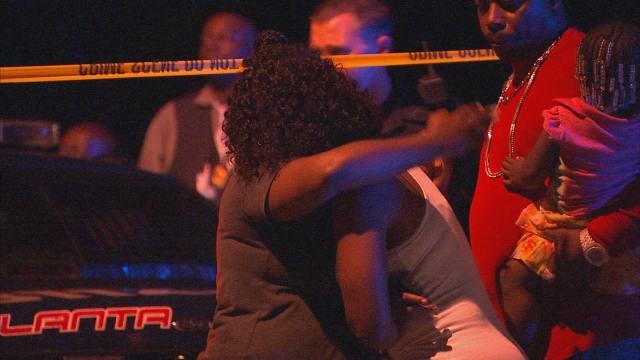 Loved ones of victim embrace at scene of killing.